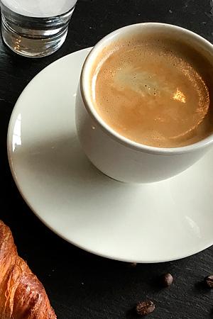 farry coffee: Kaffee aus eigener Röstung. Tasse mit Wasserglas und Croissant. Fotografin: Yvonne Kornas.