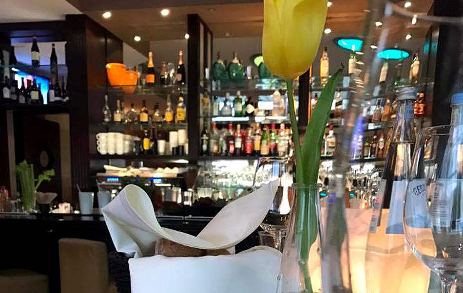 Eingedeckter Tisch mit Bar im Hintergrund. Fotografin: Natali.